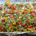 Loaded Sheetpan Nachos for a crowd! Meats, beans, cheese, veggies, cilantro and salsa make up this crowd-please nacho dish!